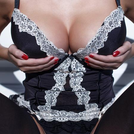 tetas: Mujer atractiva en corsé sosteniendo sus enormes tetas, primer plano