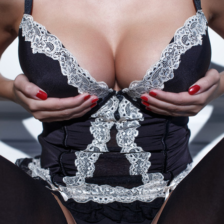 tits: Sexy woman in corset holding her huge tits, closeup Stock Photo