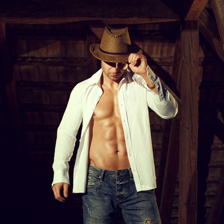 macho man in hat and shirt posing in barn Stockfoto