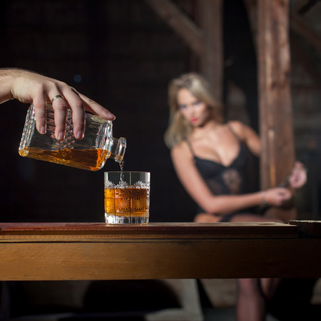 handcuffs female: Man pour whiskey for sexy woman lover