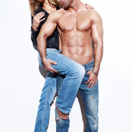 pareja desnuda: Pareja atractiva de moda que presenta en la pared blanca