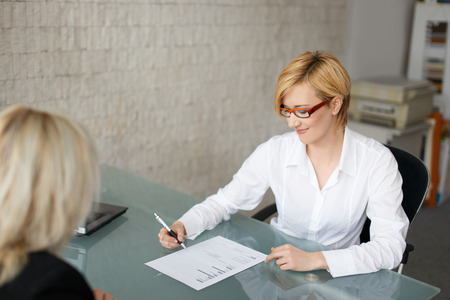Blonde businesswoman fill out a form in office Stockfoto