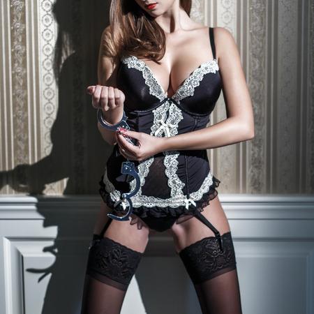 tetas: Mujer atractiva en manillas de cierre de corsé en la pared de la vendimia Foto de archivo