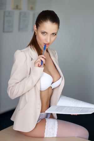 Empresaria atractiva se sienta en el escritorio en la oficina