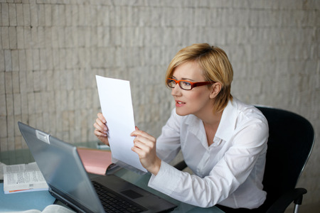 angry blonde: Blonde businesswoman in glasses reading letter, bad news