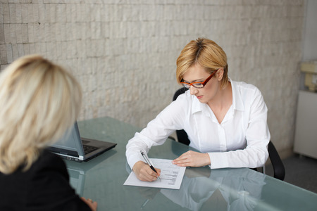 fill fill in: Young businesswoman fill out the form in office