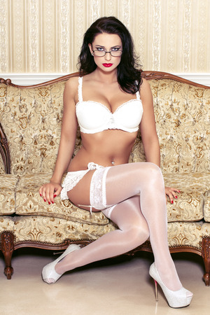 sexy boobs: Sexy woman in glasses and white underwear sit on sofa