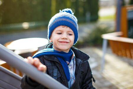 pompon: Little boy in winter pompon cap, outdoor portrait