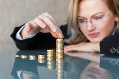 pension fund: Blonde businesswoman in glasses building growing one euro columns, saving money concept. Stock Photo