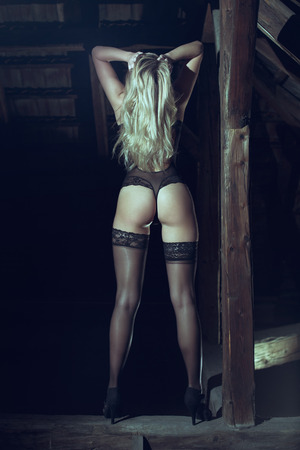 black sex: Sexy blonde woman in underwear showing ass in black transparent corset and stockings. Posing on timer in barn.