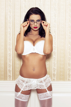 hot sex: Sexy woman in white bra holding glasses at vintage wall