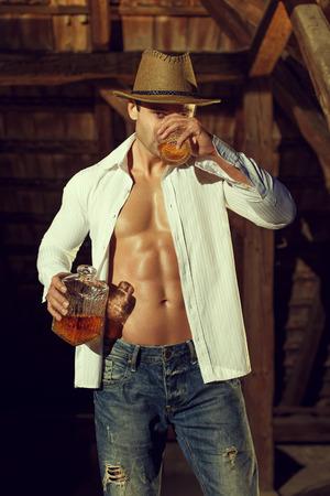 cuerpos desnudos: Vaquero atractivo hombre macho copa de whisky en el granero Foto de archivo