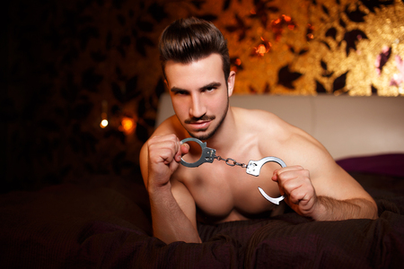 men sex: Sexy macho man with handcuffs laying on bed, bdsm Stock Photo