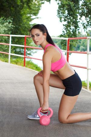 mujer arrodillada: Mujer morena de rodillas con pesas rusas rosa Foto de archivo