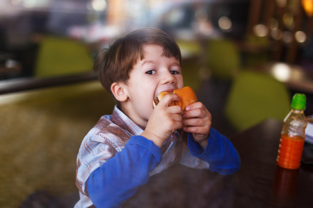 Fat kid: Little boy eat hamburger behind glass in fast food restaurant Stock Photo
