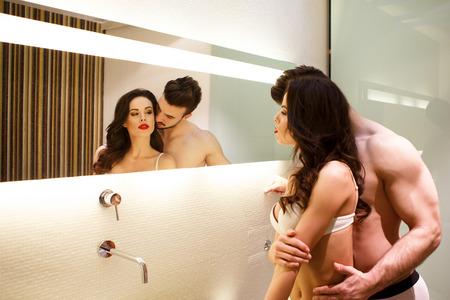 sexo pareja joven: Pareja joven y atractiva que presenta en el espejo del ba�o