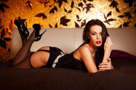 mujeres eroticas: Mujer atractiva en medias tirado en la cama por la noche Foto de archivo