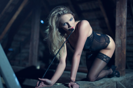 Sensual woman in underwear and whip crawling on timber in barn at night, bdsm
