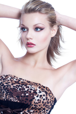 high end: Young woman with blowing hair in leopard dress, high end beauty cosmetics, isolated on white