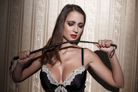 big boobs: Mujer atractiva con el látigo en la noche en la pared del vintage, bdsm