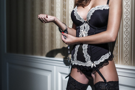 Sexy woman with big tits in corset locking handcuffs at vintage wall Archivio Fotografico