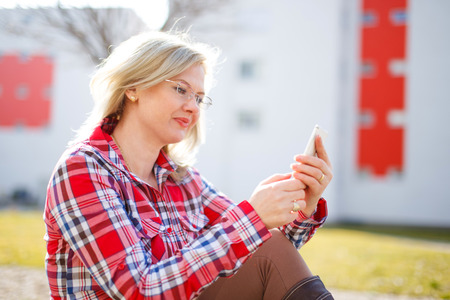 flannel: Young businesswoman reading messages outdoor at spring Stock Photo