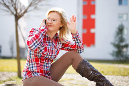 flannel: Young  businesswoman call and wave with hand. Sitting in park at spring