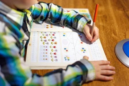 workbook: Little boy doing homework at home with pencil into maths workbook