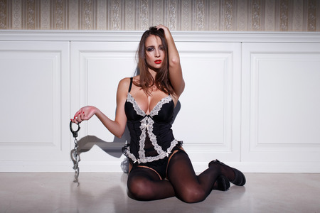 tits: Sexy woman holding handcuffs at vintage wall, bdsm