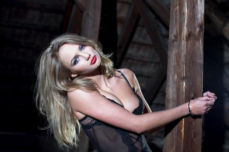 sex girl: Sensual blonde woman cuffed to timber in barn at night, bdsm