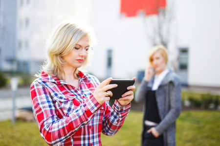 flannel: Businesswomen using tablet and calling in park Stock Photo