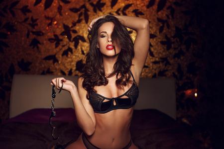 sexo pareja joven: Sexy mujer arrodillada y celebración de las esposas en la cama, bdsm