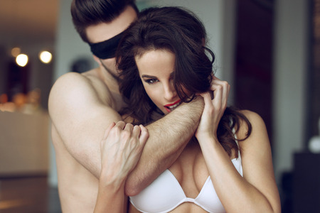 man and woman sex: Passionate couple foreplay in luxury flat, sexy woman in bra bite man arm, young lover with lace eye cover Stock Photo