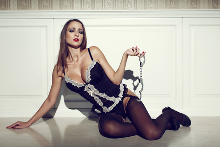 sex toys: Sensual woman holding handcuffs, closed eyes, vintage style
