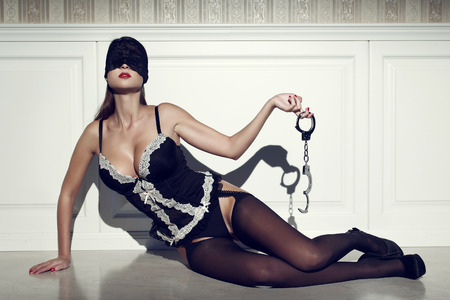 Sexy woman in lace eye cover with handcuffs, posing on floor at vintage wall Stock Photo