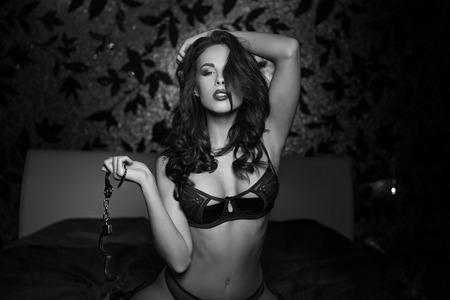 sexo pareja joven: Mujer atractiva de rodillas y sosteniendo las esposas en la cama, bdsm, blanco y negro