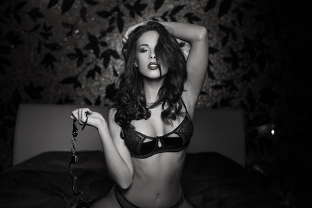 hot sex: Sexy woman kneeling and holding handcuffs on bed, bdsm, black and white