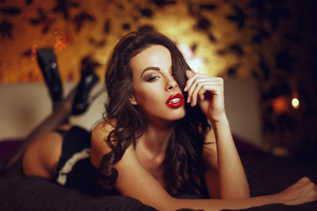Mujer atractiva en ropa interior posando en la cama en la habitación de hotel, amante sensual