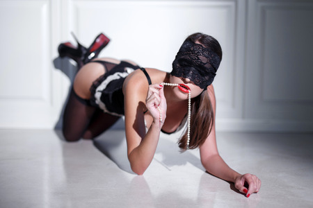 erotic fantasy: Sexy woman in lace eye cover and underwear posing on floor, pearls in mouth, sensuality Stock Photo
