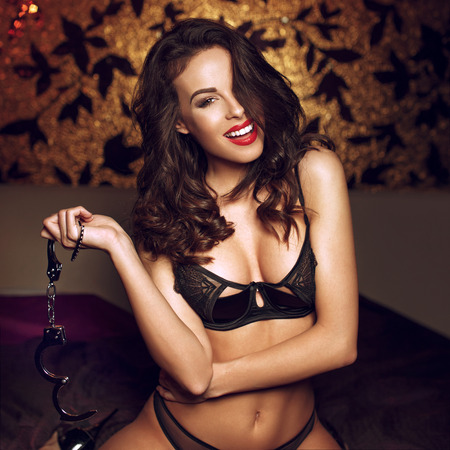 Sexy woman holding handcuffs in bedroom,