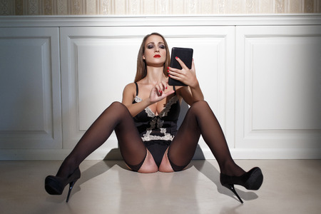 tits: Sexy woman in black underwear with tablet sit on floor at vintage wall Stock Photo
