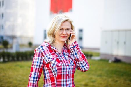 flannel: Blonde businesswoman in flannel shirt calling, outdoor portrait Stock Photo