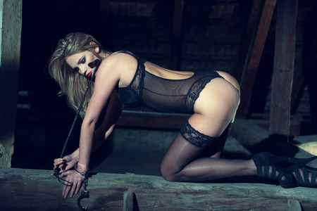 hot sex: Sexy woman kneeling on the timber in barn at night, sensuaity and bdsm