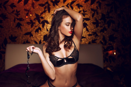 sex toys: Sexy naked woman with handcuffs in bedroom, bdsm Stock Photo