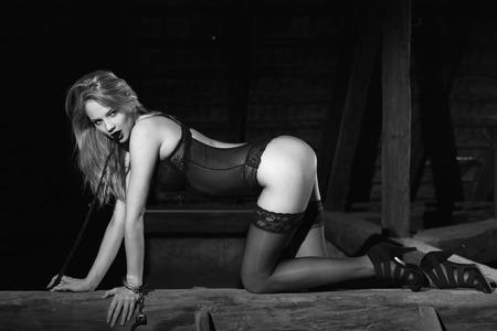 femme sexe: Femme blonde sexy en sous-v�tements � genoux sur le bois avec fouet, noir et blanc, de BD Banque d'images