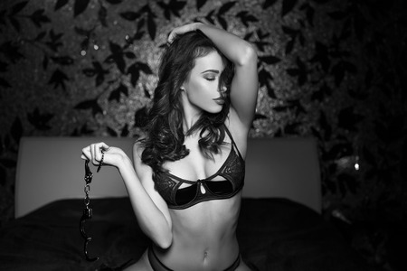 erotic women: Sexy naked woman with handcuffs in bedroom, black and white, bdsm Stock Photo