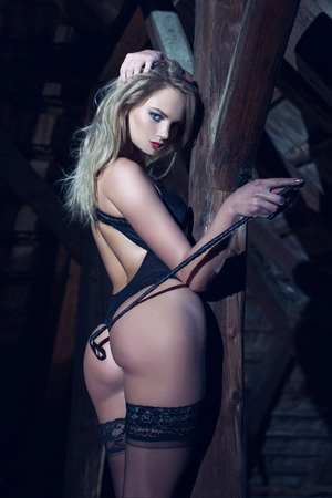 sexo pareja joven: Mujer atractiva con el l�tigo de cuero que presenta en la madera, bdsm Foto de archivo
