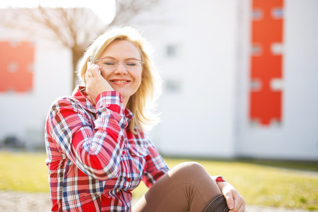 flannel: Blonde woman calling by smartphone in park after work, gossip Stock Photo