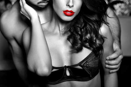 men sex: Sensual woman in underwear with young lover, passionate couple foreplay closeup, black and white, selective coloring Stock Photo