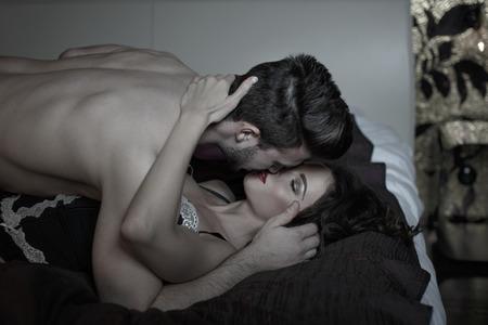 sexo pareja joven: Pareja apasionada bes�ndose en la cama por la noche Foto de archivo